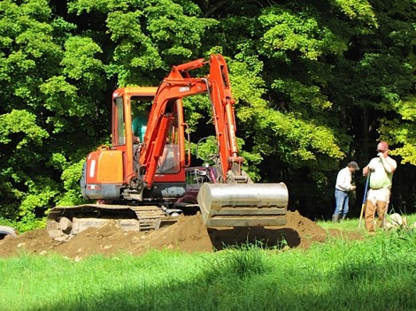 The backhoe digs a trench for the cable connecting the solar array and the author's house.