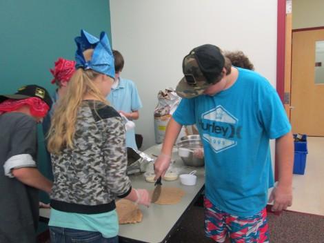 The cracker crew cuts dough into bite-size crackers. Photo: Heather Bellow