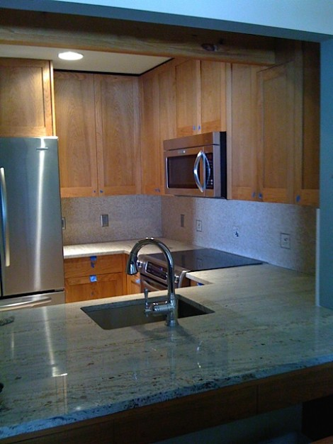the condo kitchen with granite countertops and new backsplash.